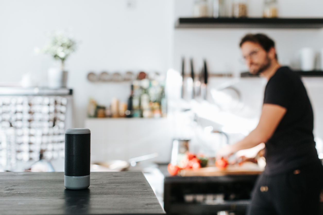 man-cooking-and-talking-to-smart-speaker